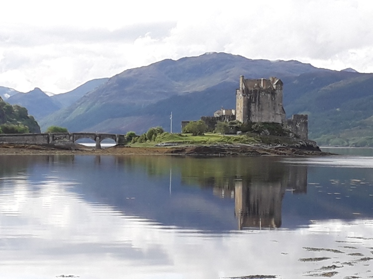 Eilean Donan Castle in Dornie. Castle looks like a 15th century castle on islet. Constantly connected by two arch bridge. Water still, mirrors the castle. Bare hill in the background.