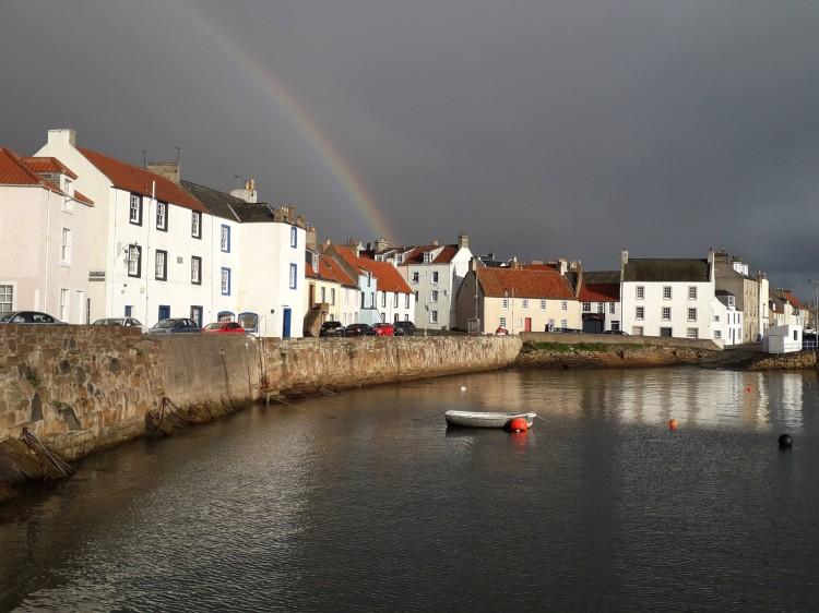 Harbour wall with one boatin the water. Above wall street lined with white painted houses and pan tiles. Rainbow above. Water all calm