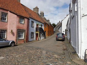 Looking up a street lined with houses 17th century. White painted on right hand side and pink, white, orange coloured houses on the left. Pan tiled. Cobbles end near the foregrougnk