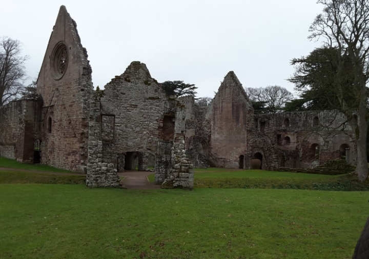 Ruins of an abbey. Whole walls are standing but other walls are missing. on grassland. Largely red and blonde sandstone.