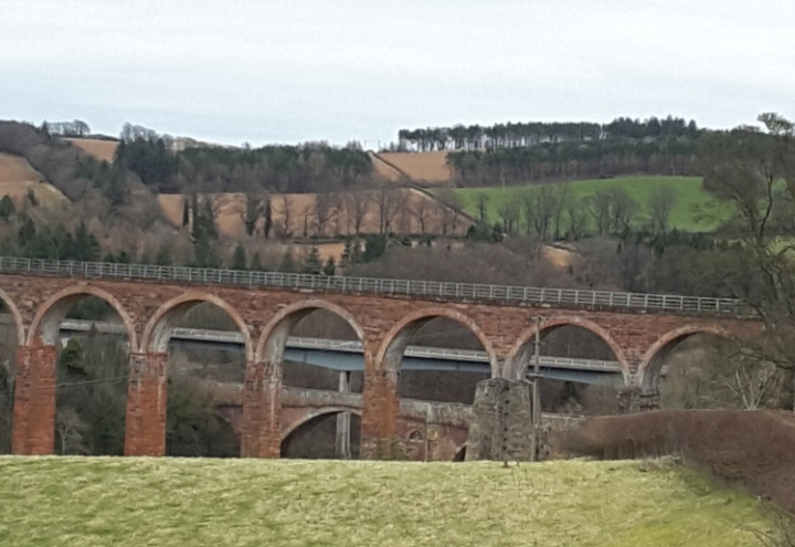 Three bridges crossing. In front the highest has 7 narrow high arches visible. This is the 1893 rail way viaduct. Behind, just under the arches is the modern road bridge from 1973. further below and behind, with much wider arches the road bridge from 1780. The older crossings are in red sand stone. In the foreground the edge of grassland. on the other side of the valley fields