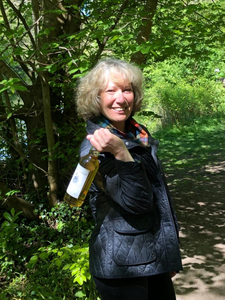 Ruth on a wooded path. Looking back over shoulder with whisky bottle thrown back over shoulder in hand. Smiles into camera