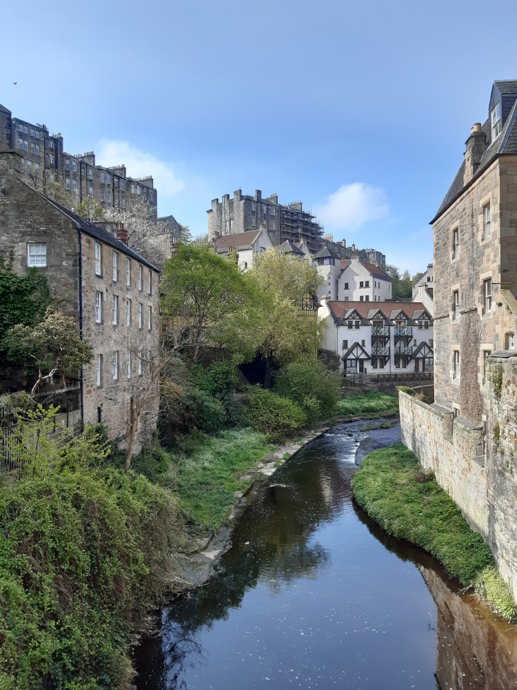 Narrow river flowing from the foreground to the back. Converted mill buildings left and right of the river. River bends to the right in the background. View on to White three storey home with wooden beams above it in the background looms the castle.