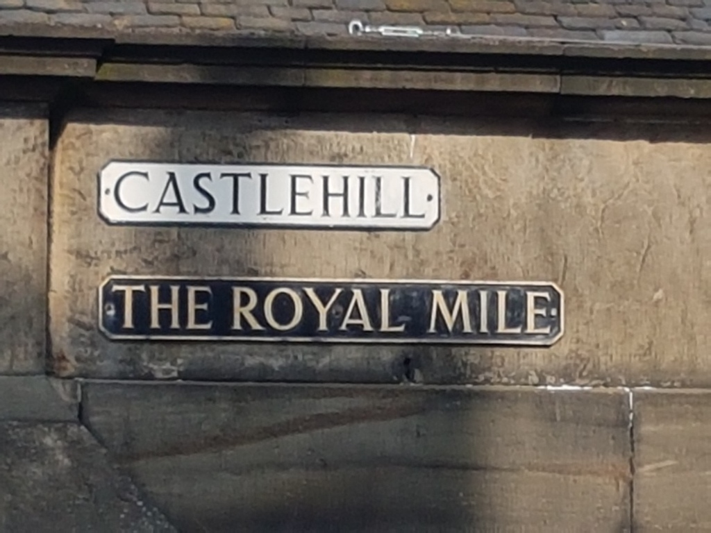 the regular street sign reading Castlehill black on white . Below is the street sign reading The Royal Mile in Gold coloured letters on black. On House wall in sandstone