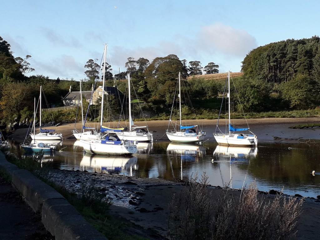 river Almond estuary at low tide taken from promenade looking over to wooded banks with ferry man's house to the left in the background. White sailing boats sitting in the water