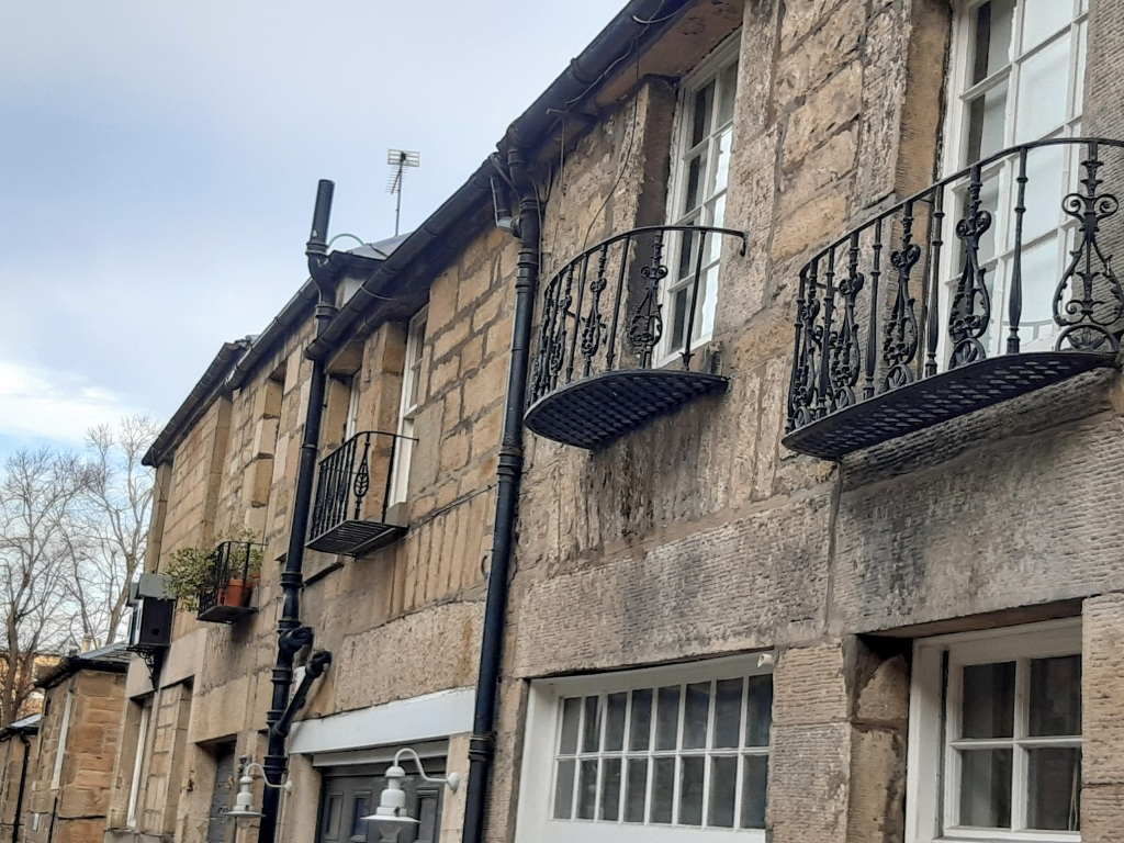 House walls in sandstone. Upper part of the buildings with decorative mini balconies, cast iron. Windows with inset frames. Black painted drain pipes. One house has flower pots out under neath the windows.