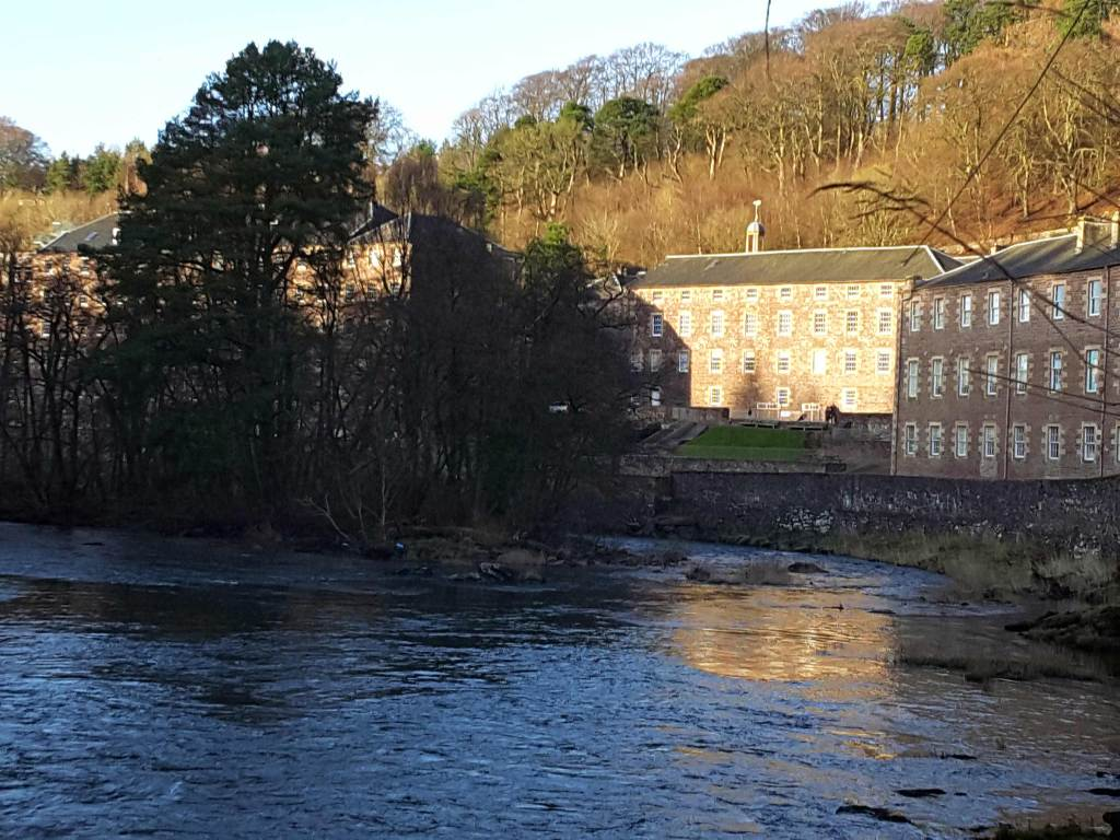 River in the foreground with some trees on on the river bank, a wall protecting the land behind. Two 3 storey brick buildings with regular windows inserted. They are the New Lanark MillsThe mills are right at the foot of a wooded hill, Trees display no foliage