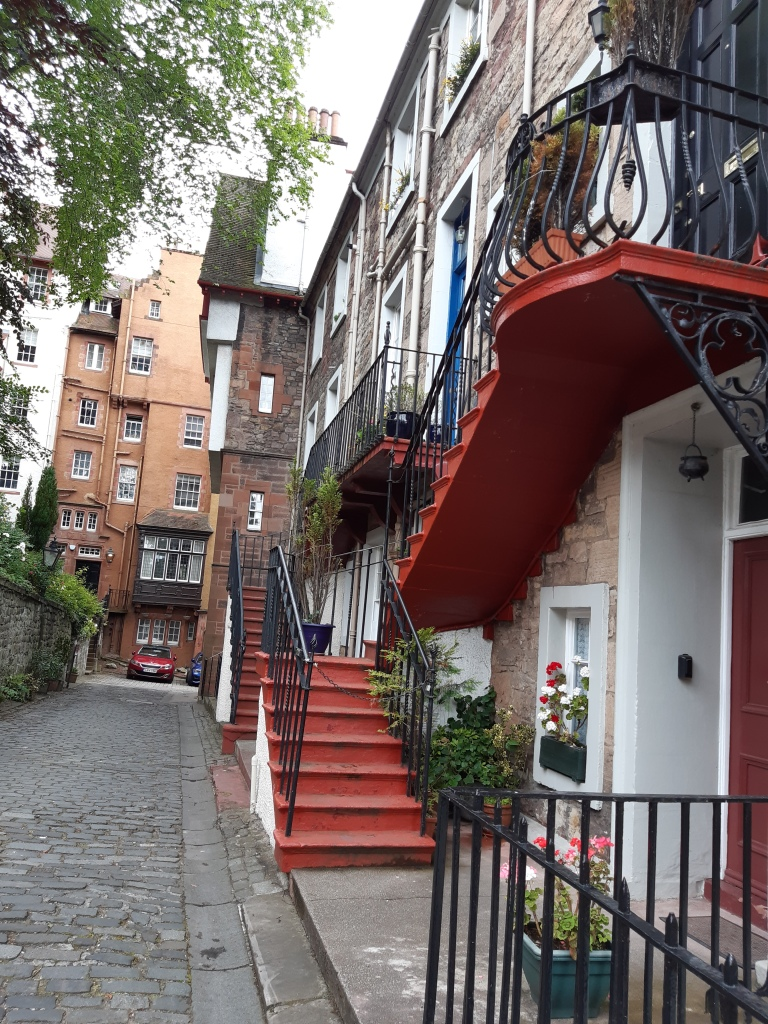 View up the street with high built homes at the end and to the right. The house at the end is burnt orange coloured and of irregular shape to the right outside steps painted red with cast iron banister. Steps leading to flats in the first and second floor. decorated with flower pots. Red door to groundfloor flat.